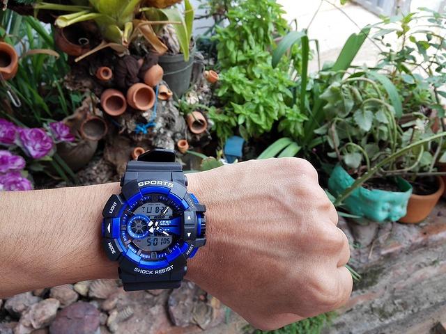 zegarek GSHOCK niebieski na nadgarstku, w tle rośliny